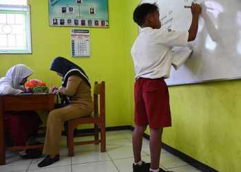 KEGIATAN PEMBELARAN : Seorang guru SD 1 Tanjung Purwokerto Selatan memberikan pendampingan kepada siswa berkebutuhan khusus dalam kegiatan pembelajaran. (60)(SM/Dian Aprilianingrum)