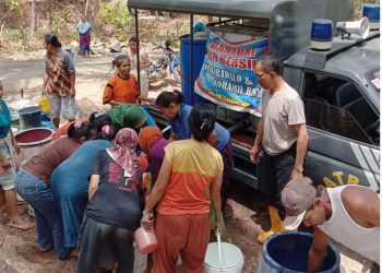DISTRIBUSI AIR BERSIH : Anggota Polsek Rawalo tengah mendistribuskan air bersih di desa yang kekurangan air Kamis  (19/9). (37)  (SM/dok)