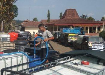ISI WADAH PENAMPUNGAN: Warga mengisi air di wadah penampungan air di Desa Karantengah, Cilongok sebelum dikirim ke wilayah krisis air bersih.