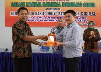 PENGHARGAAN: Dekan Fisip Unwiku, Suryoto (kiri) serahkat penghargaan kepada Wakil Ketua STIN, Kombespol Barito Mulyo Ratmono, Kamis (12/9). (SM/Nugroho PS-60)