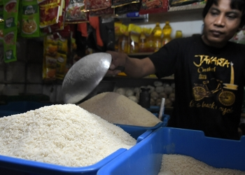 TAKAR BERAS: Pedagang sembako menakar beras pesanan pembeli, di Pasar Manis Purwokerto, Senin (2/9) (SM/Dian A)