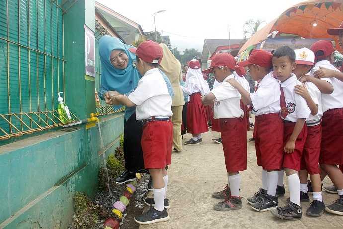 MENCUCI TANGAN: Wakil Ketua TP PKK Banjarnegara Kristiyani Syamsudin membimbing siswa mencuci tangan yang benar saat peringatan Hari Mencuci Tangan Sedunia 2019. (SM/dok)