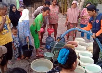 TERIMA BANTUAN: Sejumlah warga terdampak bencana kekeringan di Dusun Kawungcarang Desa Pangawaren Kecamatan Karangpucung Kabupaten Cilacap menerima bantuan air, Jumat (4/10). (SB/Akbar Teha)