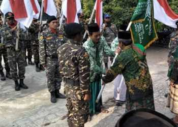 PENYERAHAN BENDERA: MWC NU Gandrungmangu Kabupaten  Cilacap menyerahkan bendera ke pengurus ranting Desa Layansari dalam kirab memperingati HSN, Minggu (20/10). (SM/dok)