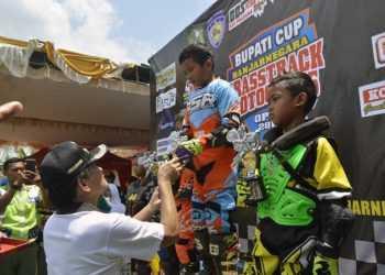 SERAHKAN PIALA: Bupati Budhi Sarwono menyerahkan piala kepada pemenang, pada penutupan Kejuaraan Grasstrack dan Motocross Bupati Cup 2019 di Sirkuit Manggul Baya, Desa Wiramastra, Kecamatan Bawang. (SM/Castro Suwito-37)