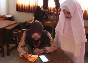 MEMILIH KETUA OSIS: Salah satu siswa menggunakan aplikasi e-voting untuk memilih Ketua dan Wakil Ketua OSIS SMKN 1 Bawang didampingi penjaga TPS yang berkostum hantu. (SM/Castro Suwito)