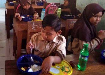MAKAN BERSAMA: Sejumlah siswa salah satu SD di Kabupaten Banyumas makan bersama dalam program gizi anak sekolah (Progas), baru-baru ini.(SM/Budi Setyawan-20)