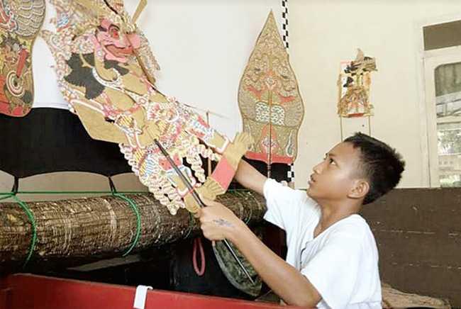 BERLATIH: Dalang bocah Arfian Dwi Kurniawan, siswa kelas 7 SMP Negeri 1 Cilacap sedang berlatih mendalang di Sanggar Ajisaka sebagai persiapan pentas Hari Wayang Nasional. (SM/Agus Sukaryanto-52)