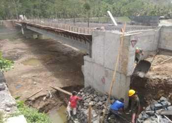 BEKERJA: Sejumlah pekerja terlihat bekerja membuat pondasi di bawah bagian Jembatan Janggawana, Desa Tiparkidul, Kecamatan Ajibarang kemarin.
