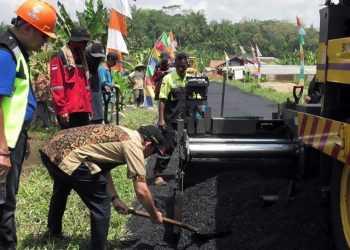 UJI COBA: Bupati Achmad Husein meratakan aspal dengan sekop saat uji coba aspal campuran plastik di Desa Kedungwuluh Lor, Kecamatan Patikraja, baru-baru ini. (SM/dok humas Pemkab Banyumas)