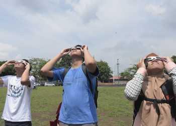 MENGAMATI GERHANA MATAHARI: Anggota komunitas astronom amatir menggunakan teleskop atau teropong bintang saat menyaksikan gerhana matahari di Alun Alun Purwokerto, Kamis (26/12). (SM/Dian Aprilianingrum)