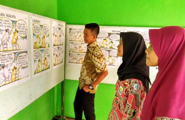 MELIHAT-LIHAT: Sejumlah pelajar melihat-lihat komik strip yang dipamerkan di dinding Aula SMPN 5 Purwokerto, Rabu (4/12). (SM/dok)