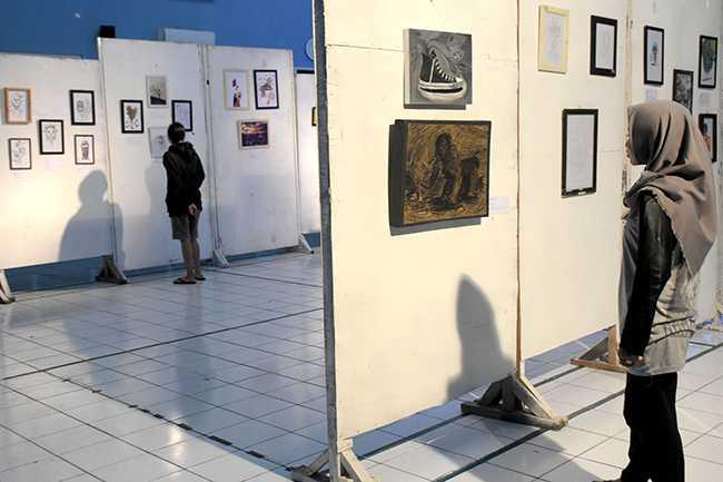 "MELIHAT-LIHAT: Pengunjung melihat-lihat karya yang dipajang pada pameran ulang tahun Unit Kegiatan Mahasiswa Seni Rupa ""Senru"" IAIN Purwokerto, Minggu (1/12). (SM/Dian Aprilianingrum-37)"