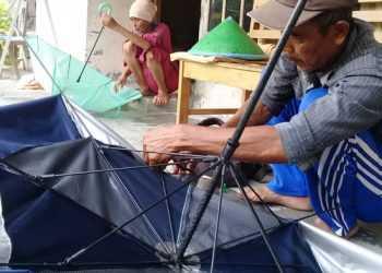 SERVIS PAYUNG: Seorang tukang servis payung asal Desa Cinangsi, Kecamatan Gandrungmangu, Kabupaten Cilacap, Mad Husen memperbaiki payung rusak milik warga, Kamis (19/12).(SM/Teguh Hidayat Akbar-52)