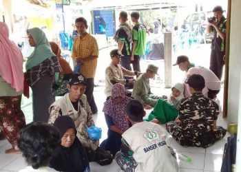 LAKUKAN PENGOBATAN: Banser Husada Banyumas bersama siswa guru SMK Maarif NU 2 Ajibarang melakkan pengobatan gratis kepada korban angin kencang di Grumbul Tigasan, Desa Sawangan, kemarin.
