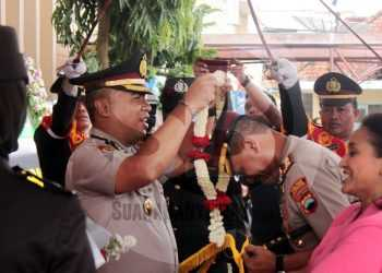 KALUNGKAN BUNGA: AKBP Aris Yudha Legawa mengalungkan rangkaian bunga kepada AKBP I G A Perbawa Nugraha saat upacara pedang pora pisah sambut Kapolres Banjarnegara. (SM/Castro Suwito-52)