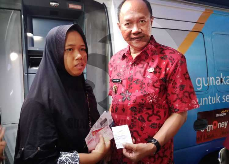 BANTUAN PKH: Salah satu KPM PKH, menunjukkan uang bantuan yang diterima setelah mengambil di gerai ATM berjalan, bersama Wakil Bupati Banyumas Sadewo Tri Lastiono, Selasa (14/1). (SM/Gayhul Dhika Wicaksana-60)