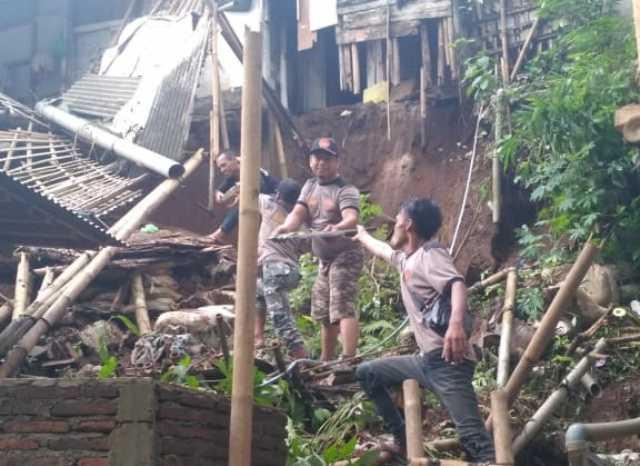 BERSIHKAN PUING: Personel Banser dan masyarakat membersiihkan puing reruntuhan rumah rusak akibat longsor di Desa Gununglurah, Cilongok, Sabtu (11/1).