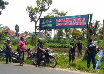 PASANG SPANDUK: Personel Ansor-Banser Kecamatan Kedungbanteng memasang spanduk 'Tolak Togel' di beberapa ruas jalan utama, Kamis (20/2).