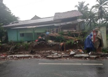 SINGKIRKAN PUING: Warga singkirkan puing reruntuhan tembok pagar SD 1 Kracak, Kecamatan Ajibarang yang ambruk Sabtu (22/2) sore.
