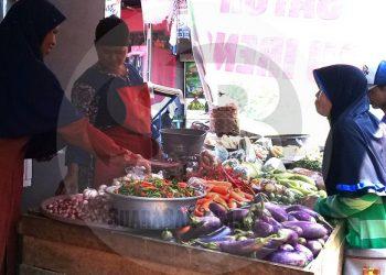 MELAYANI PEMBELI: Seorang pedagang cabai dan bawang melayani pembeli di Pasar Induk Majenang, Kabupaten Cilacap, baru-baru ini. (SM/Teguh Hidayat Akbar)