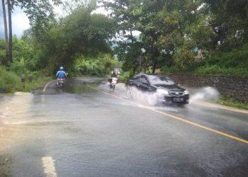 MELUAP KE JALAN: Air luapan drainase menggenangi jalan nasional Ajibarang-Wangon tepatnya Desa Windunegara, Kecamatan Wangon, Selasa (4/2) petang.