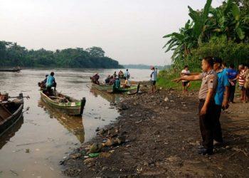 LOKASI KEJADIAN: Anggota Polsek Kesuguhan dan warga sedang menunjukan Depo Pasir Sungai Serayu Desa Pesanggrahan, Kecamatan Kesugihan tempat korban tenggelam.(SM/Agus Sukaryanto)