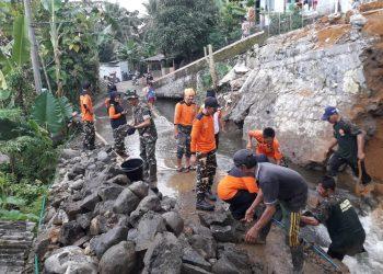 KERJA BAKTI: Masyarakat, TNI-Polri, Tagana, Bagana, BPBD Banyumas kerja bakti menyingkirkan puing tebing pengaman irigasi yang longsor Minggu (15/3).