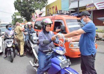 BAGIKAN MASKER: Bupati Achmad Husein terlibat langsung membagikan masker gratis kepada pengguna jalan didepan Alun-alun Purwokerto, Senin (23/3). Ada 1.000 makser dan 400 botol hand sanitizer dibagikan secara gratis.(SM/Agus Wahyudi)