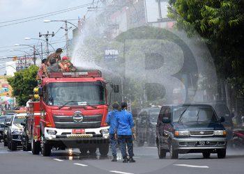 CAIRAN DISINFEKTAN : Bupati Banyumas Achmad Husein didampingi unsur Forkompimda, menyemprotkan cairan disinfektan menggunakan mobil pemadam kebakaran di Jalan Jendral Soedirman Purwokerto, Kamis (26/3).(60) (SM/Dian Aprilianingrum)