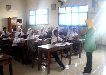 AKTIVITAS MENGAJAR :Seorang guru di salah satu SMP di Kabupaten Banyumas sedang melakukan aktivitas mengajar di dalam kelas.(60) (SM/Budi Setiawan)