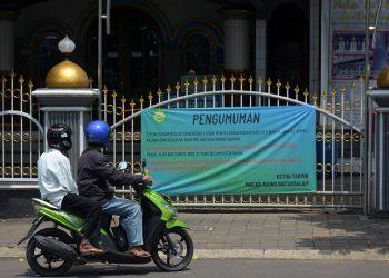 DITUTUP SEMENTARA: Spanduk pemberitahuan masjid ditutup secara sementara dipasang di depan gerbang Masjid Agung Baitussalam Purwokerto, Jumat (27/3) (SM/Dian Aprilianingrum)