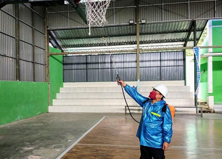 PENYEMPROTAN-Petugas KONI melakukan penyemprotan disinfektan di indoor bola basket Banjarnegara. (SM/dok).