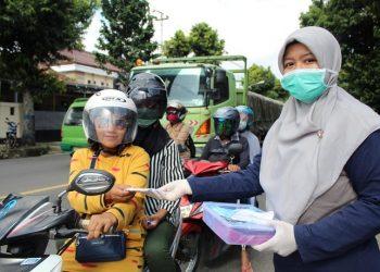 BAGIKAN MASKER: Siswa SMKN 1 Bawang membagikan masker kepada pengendara yang sedang berhenti di lampu merah saat aksi sosial untuk membantu mencegah penularan virus korona. (SM/Castro Suwito)