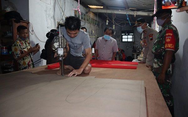 MEMOTONG BAHAN : Salah seorang pekerja di sentra konveksi Desa Kebutuhduwur Kecamatan Pagedongan sedang memotong bahan yang akan dibuat menjadi alat pelindung diri (APD) bagi tenaga kesehatan dan sukarelawan yang menangani penyakit Covid-19. (SM/Castro Suwito)