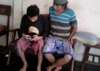UJIAN SEKOLAH:Dengan didampingi orang tuanya, salah satu siswa SMP 5 Purwokerto mengerjakan ujian sekolah secara online.(SM/dok)