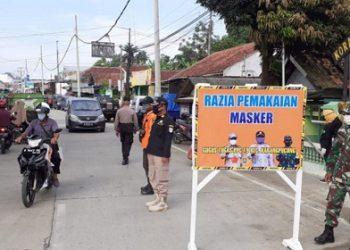 RAZIA: Petugas melakukan razia pemakaian masker di sekitar area Pasar Desa Karangpucung, tepatnya di jalan raya depan Koramil 15 Karangpucung, Kabupaten Cilacap, Minggu (10/6). (SM/dok)