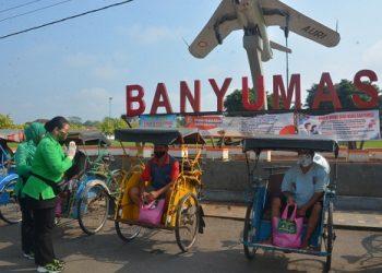 JUMAT BERKAH: Ketua Persit Kartika Chandra Kirana Koorcab Rem 071 Anita Dani Wardhana, berbagi dengan para pengemudi becak di Alun-Alun Banyumas, Jumat (8/5). (SM/dok)