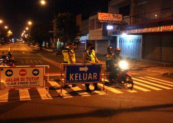 MELINTAS: Pengendara motor melintas di pertigaan Sawangan Purwokerto yang dijaga oleh sejumlah aparat, Rabu (13/5) malam. (SM/Nugroho PS)
