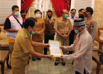 PASIEN SEMBUH: Bupati Banjarnegara Budhi Sarwono memberikan surat keterangan kepada pasien yang dinyatakan sembuh dari Covid-19 setelah menjalani perawatan dan hasil uji swab evaluasi yang dinyatakan negatif. (SM/Castro Suwito)