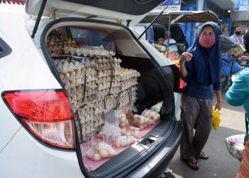 LAYANI PEMBELI: Pedagang melayani warga yang akan membeli telur infertil dagangannya di Pasar Wage Purwokerto, Rabu (13/5) (SM/Dian Aprilianingrum)