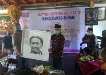 TERIMA LUKISAN: Ahmad Tohari menerima kado lukisan dari pelukis kiai NU Djoko Susilo saat tasyakuran 72 tahun Ahmad Tohari di Gubug Carablaka, Tinggarjaya, Jatilawang, Banyumas, Sabtu (13/6).