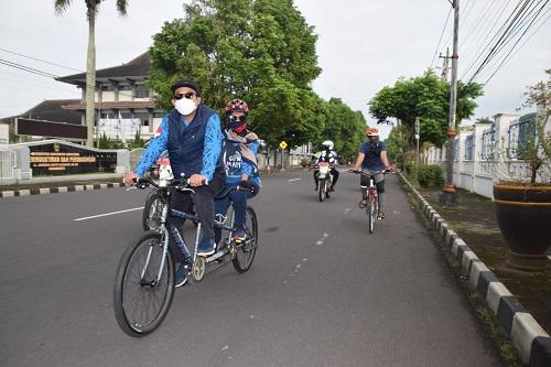 BONCENGAN : Bupati Achmad Husein bersama istrinya, Erna Husein berangkat ke kantor naik sepeda breboncengan (berduaan), Jumat (19/6) saat melintas di Jl Gatot Subroto Purwokerto. (SB/dok)