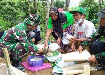 MENYANTAP MAKANAN : Anggota Koramil 15/Pekuncen/Kodim 0701/Banyumas bersama warga menyantap makanan di lokasi sasaran fisik TMMD Desa Petahunan. (SB/dok)