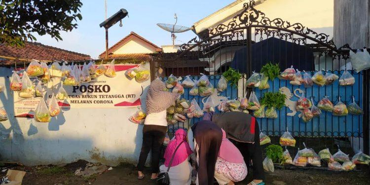 SEMBAKO CANTHEL: Sejumlah warga Ajibarang Wetan, Kecamatan Ajibarang mengambil sembako, lauk atau sayur sembako canthel yang diletakan di pintu pagar salah satu warga desa setempat, Jumat (26/6) lalu.(SM/doc)
