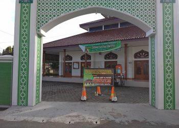 PAPAN PENGUMUMAN: Papan pengumuman mengenai penutupan masjid, terpasang di pintu gerbang Masjid Jami' Al Ma'wa, Jalan Soekarno-Hatta Cilacap, Kamis (4/6).  (SB/Gayhul Dhika Wicaksana)