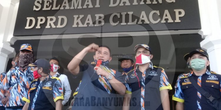 TEMUI MASSA: Ketua DPRD Cilacap, Taufik Nurhidayat (memegang mic) menemui massa GMBI setempat yang menggelar aksi damai di halaman gedung dewan, Senin (29/6). (SB/Teguh Hidayat Akbar)