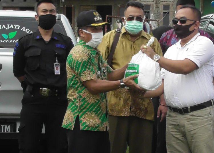 SERAHKAN BANTUAN: Presiden Komisaris PT PJ Agrinus Darsono menyerahkan bantuan paket sembako untuk warga terdampak Covid-19 melalui Camat Banjarmangu Gigih Sundoro. (SB/Castro Suwito-2)