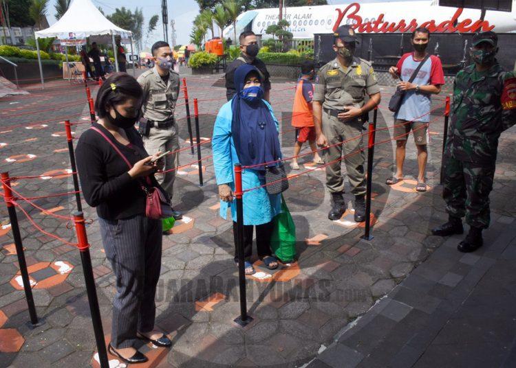 JAGA JARAK: Pengunjung menjaga jarak saat mengantre di pintu masuk Lokawisata Baturaden saat simulasi pembukaan objek wisata tersebut dengan penerapan protokol kesehatan, Sabtu (27/6). (SB/Dian Aprilianingrum-2)