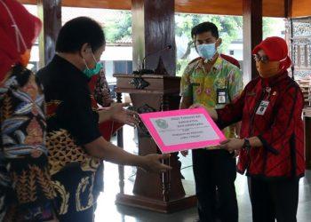 SERAHKAN BANTUAN: Pejabat dari Dinkes Jawa Tengah dr Atin Suhesti menyerahkan paket bantuan Jogo Tonggo Kit secara simbolis kepada Bupati Banjarnegara, Budhi Sarwono untuk didistribusikan ke 278 desa dan kelurahan. (SB/dok)